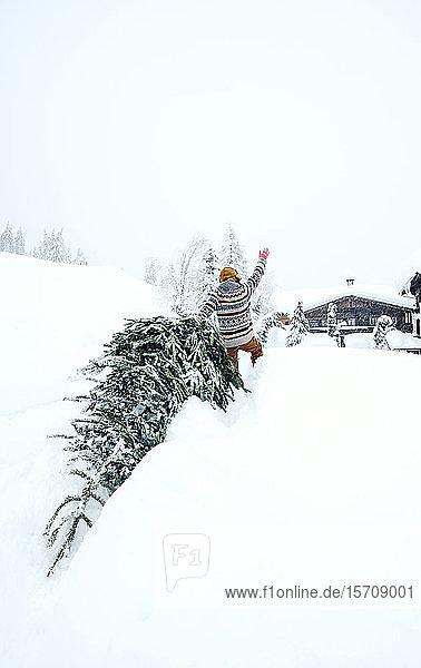 Mann kommt nach Hause  winkt und zieht Weihnachtsbaum im Schnee