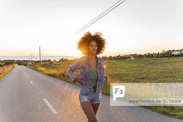 Junge Frau geht bei Sonnenuntergang auf der Straße  Ibiza