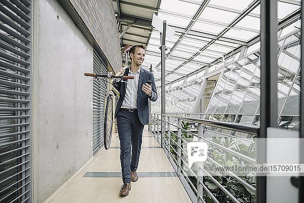 Lächelnder Geschäftsmann mit Handy mit Fahrrad in modernem Bürogebäude