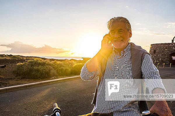 Älterer Mann benutzt Smartphone auf dem Fahrrad bei Sonnenuntergang  Teneriffa