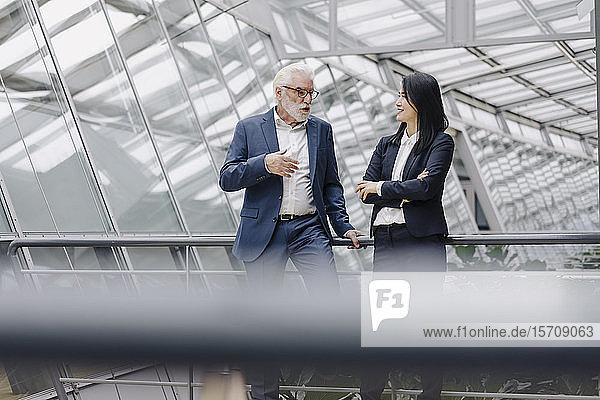 Geschäftsmann und Geschäftsfrau im Gespräch in modernem Bürogebäude