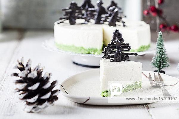 Ein Stück Käsekuchen ohne Backen  dekoriert mit Schokoladen-Weihnachtsbäumen auf einem Teller