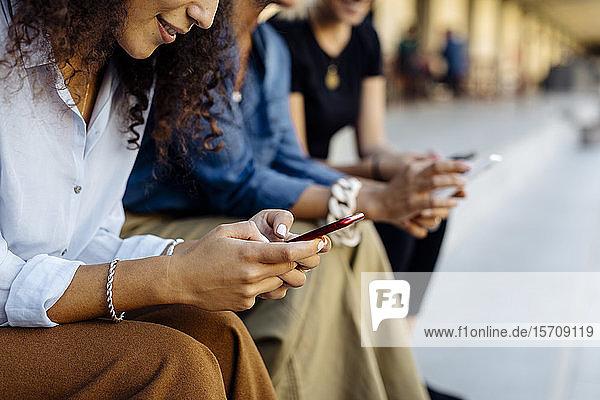 Drei Frauen sitzen auf Stufen in einer Reihe und benutzen Smartphones Drei Frauen sitzen auf Stufen in einer Reihe und benutzen Smartphones