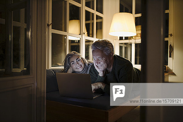 Happy senior couple lying on couch at home at night using laptop