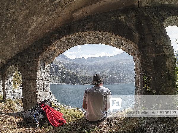 Italien  Wanderer sitzt unter einer Brücke und blickt auf den Lago di Salarno