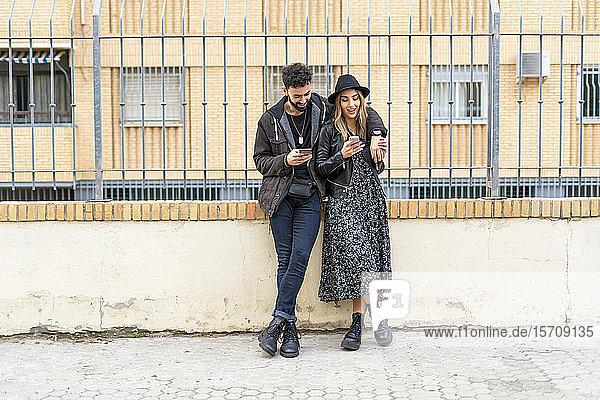 Junges Ehepaar in der Stadt bei der Benutzung ihres Mobiltelefons