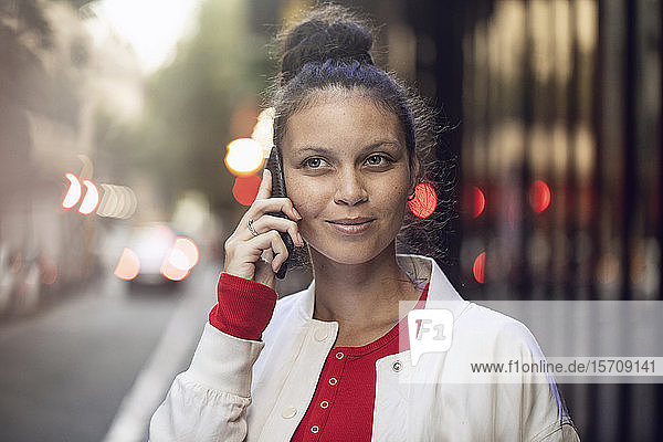 Portrait of young woman on the phone in the city