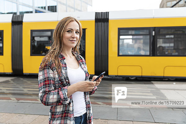 Portrait of a smiling woman in the city with a tram in the background  Berlin  Germany