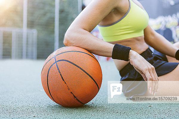 Junge Frau sitzt und ruht sich auf Basketball aus