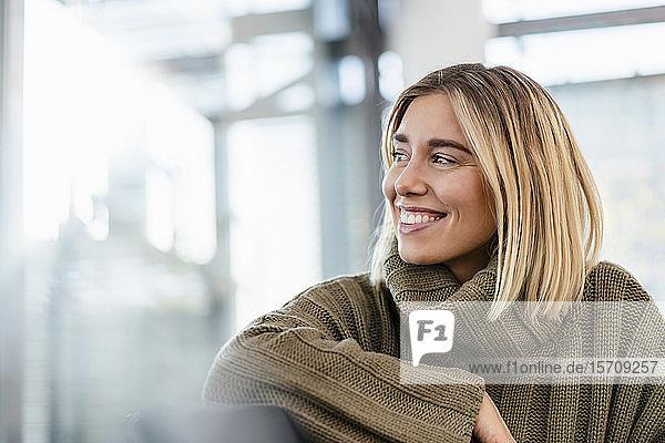 Lächelnde junge Frau sitzt im Wartebereich und schaut sich um