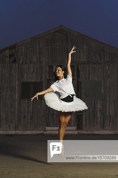 Ballerina  die abends vor einer Holzhütte tanzt