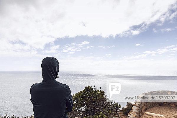 Rückenansicht eines Mannes in Kapuzenjacke mit Blick auf das Meer  Cape Point  Westkap  Südafrika