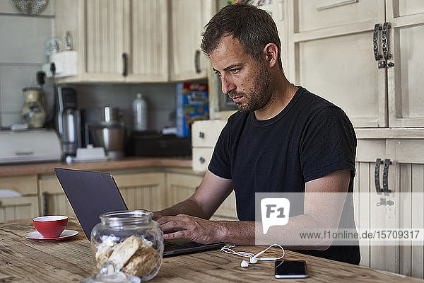 Man working from home  sitting at kitchen table  using laptop and smartphone