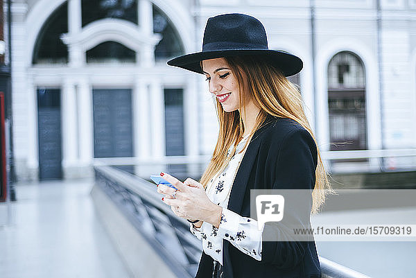 Lächelnde junge Frau mit Hut  die am Bahnhof mit dem Handy telefoniert
