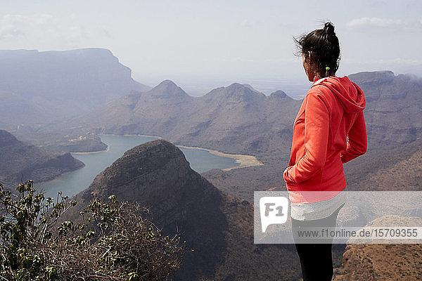 Frau  die auf einem Hügel steht und die wunderschöne Landschaft unter sich genießt  Blyde River Canyon  Südafrika.
