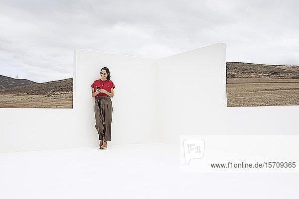 Geschäftsfrau mit Smartphone  stehend an weißer Wand