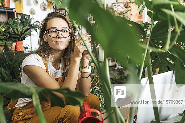 Portrait of a young woman having a coffee break in a small gardening shop
