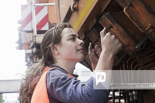 Weibliche Technikerin untersucht Lastwagen