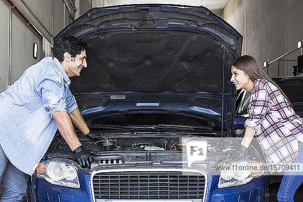Seitenansicht eines fröhlichen  ungezwungenen Mannes und einer fröhlichen Frau  die mit geöffneter Motorhaube am Auto stehen und sich gegenseitig bei der Teamarbeit in Madrid anschauen