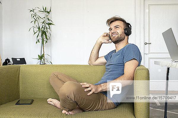 Lächelnder Mann sitzt im Büro auf der Couch und hört Musik