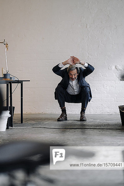 Senior businessman doing gymnastics in office
