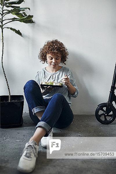 Geschäftsfrau  die im Büro auf dem Boden sitzt und Mittagspause macht