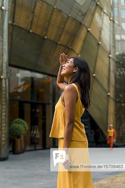 Porträt einer modischen  gelb gekleideten Frau mit Blick nach oben