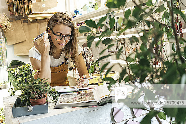 Young woman with smartphone taking notes in a small gardening shop