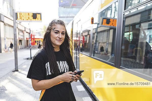 Porträt einer tätowierten jungen Frau mit Smartphone an einer Straßenbahnhaltestelle  Berlin  Deutschland