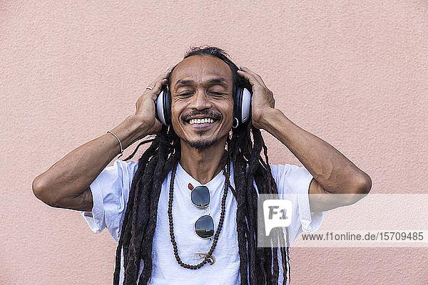 Porträt eines reifen Mannes mit Dreadlocks und Kopfhörern  der mit geschlossenen Augen Musik hört
