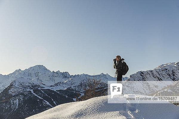 Frau beim Fotografieren einer winterlichen Berglandschaft  Valmalenco  Italien