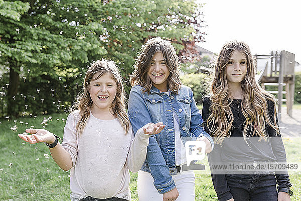 Portrait of three happy girls surrounded by dandelion seeds