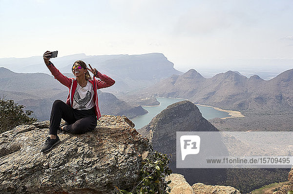 Woman taking a selfie with her cell phone with a beautiful landscape background  Blyde River Canyon  South Africa