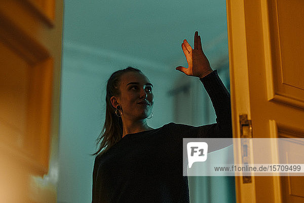 Young woman in shadow and light at open door raising her hand