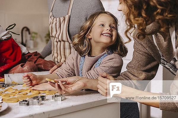 Glückliche Familie bereitet in der Küche Weihnachtsplätzchen zu