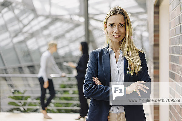 Porträt einer selbstbewussten jungen Geschäftsfrau in einem modernen Bürogebäude mit Kollegen im Hintergrund