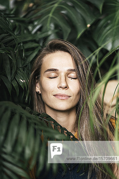Portrait of a young woman with closed eyes amidst green plants