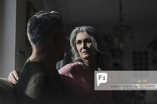 Serious senior couple sitting on couch at home in shadow