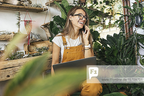 Laughing young woman on the phone in a small gardening shop