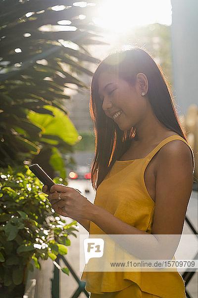 Lächelnde Frau steht im Gegenlicht und schaut auf ihr Handy