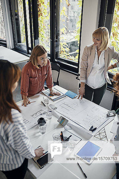 Businesswomen having a meeting in office with blueprints on table