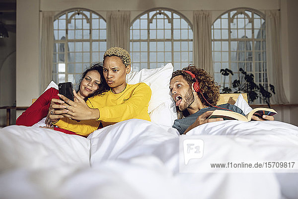 Happy friends having fun in bed at home with smartphone