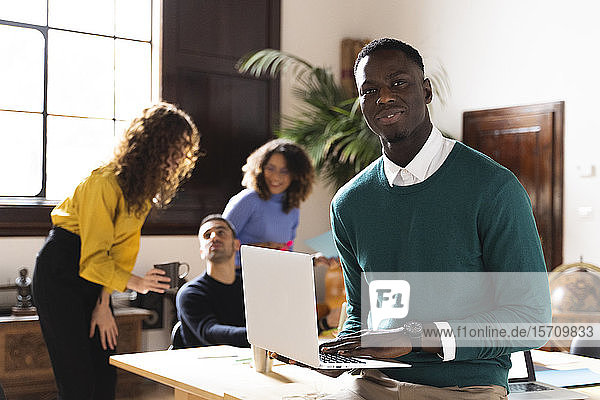 Portrait of a confident man in office using laptop with colleagues in background