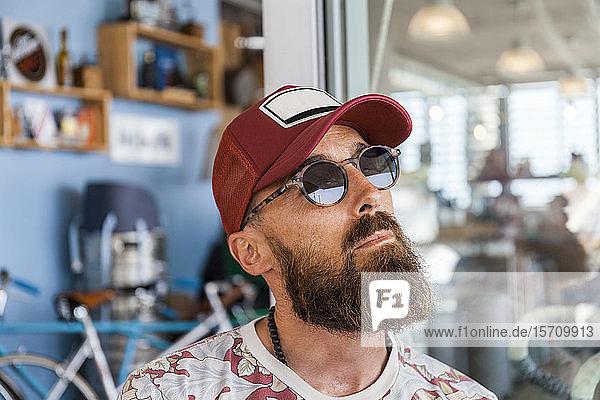 Matuer Mann mit rotem Basecap und Sonnenbrille
