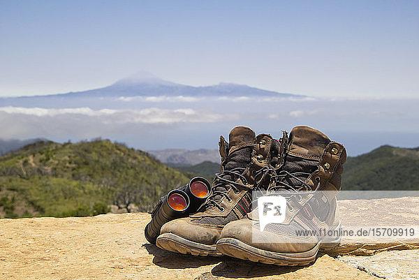 Spanien  Kanarische Inseln  La Gomera  Fernglas und braune Wanderstiefel auf dem Gipfel des Garajonay mit dem Teide-Vulkan im fernen Hintergrund