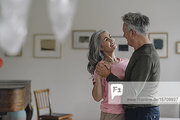 Glückliches älteres Paar tanzt zu Hause im Wohnzimmer