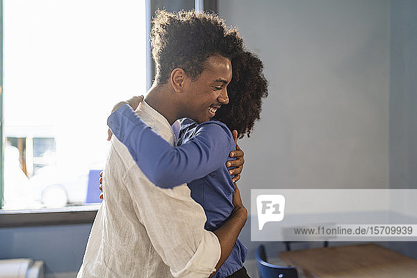 Students embracing each other in a cafe