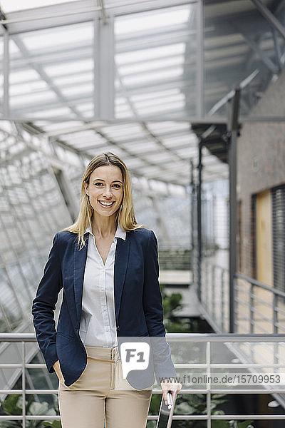 Porträt einer lächelnden jungen Geschäftsfrau in einem modernen Bürogebäude