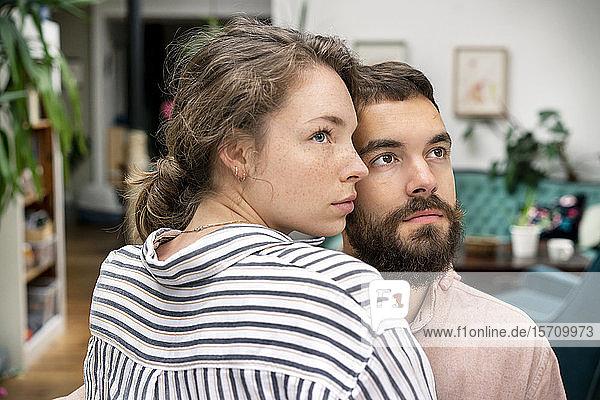 Geschwungenes Paar mit umgebundenen Armen  das unsicher aussieht