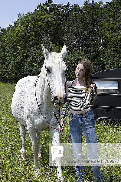 Portrait of teeange girl with horse on a meadow